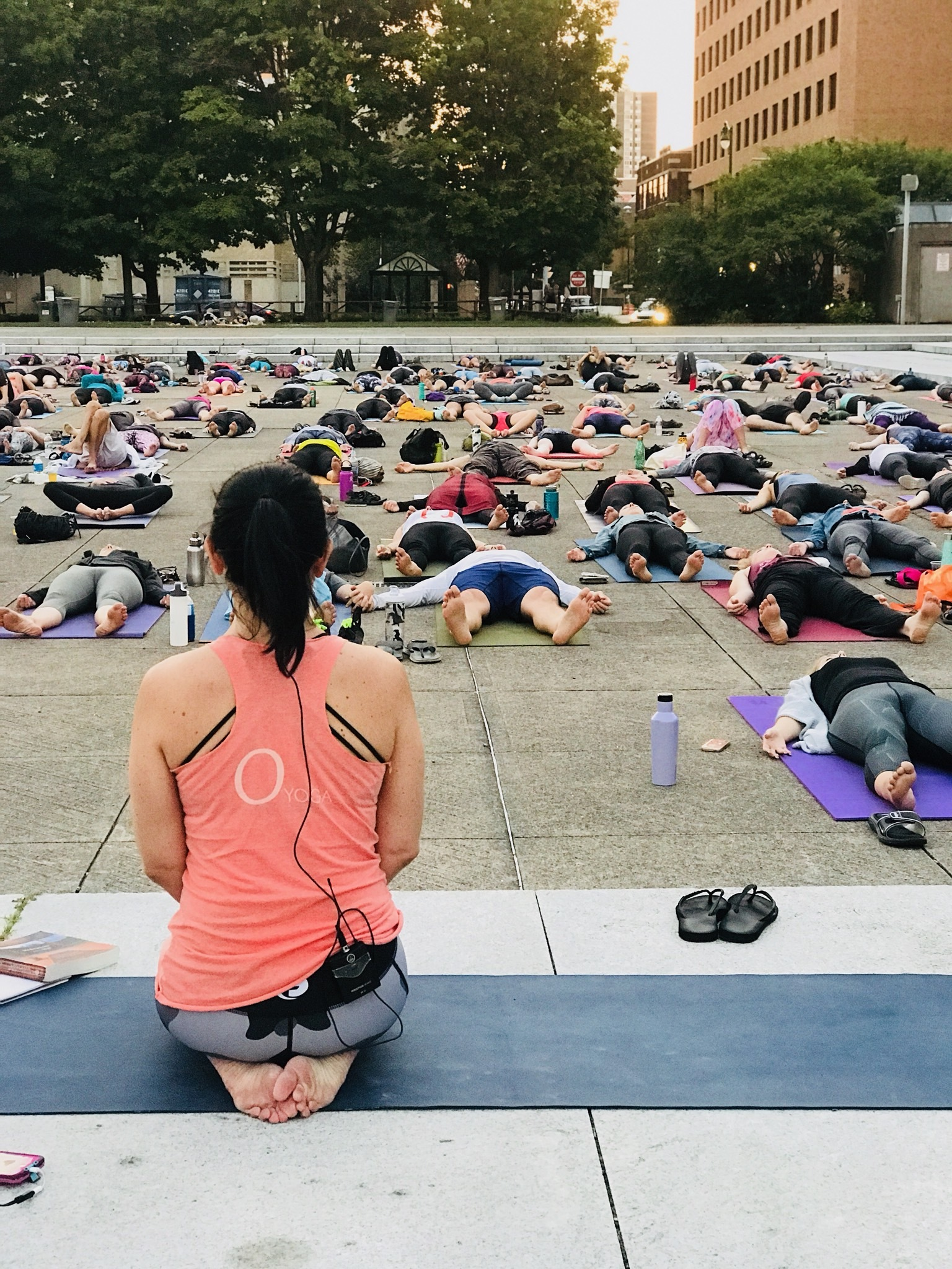 Tiffany Cagwin leading an outdoor yoga session in a city