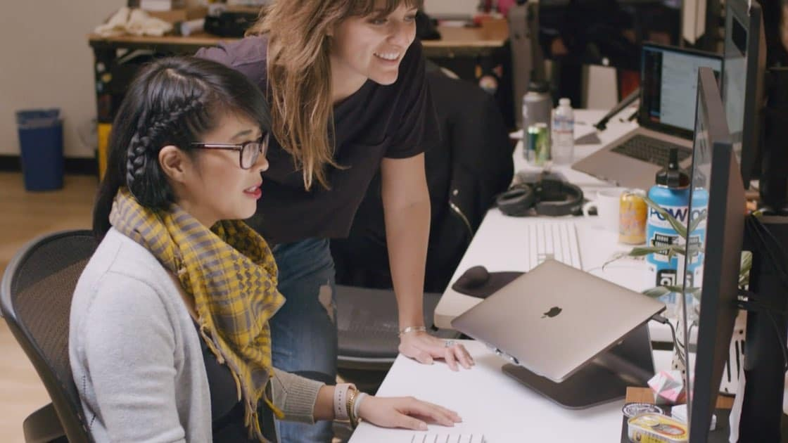 Salesforce employees collaborate on a design project while looking at a monitor together.