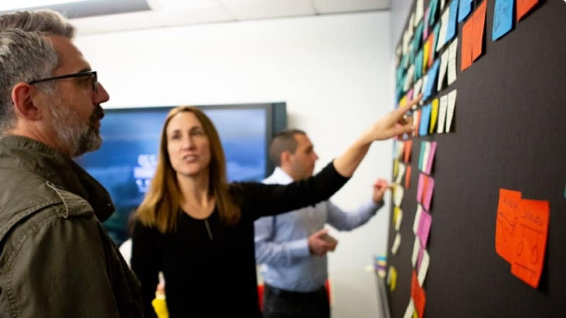 Microsoft employees collaborate on a board with sticky notes