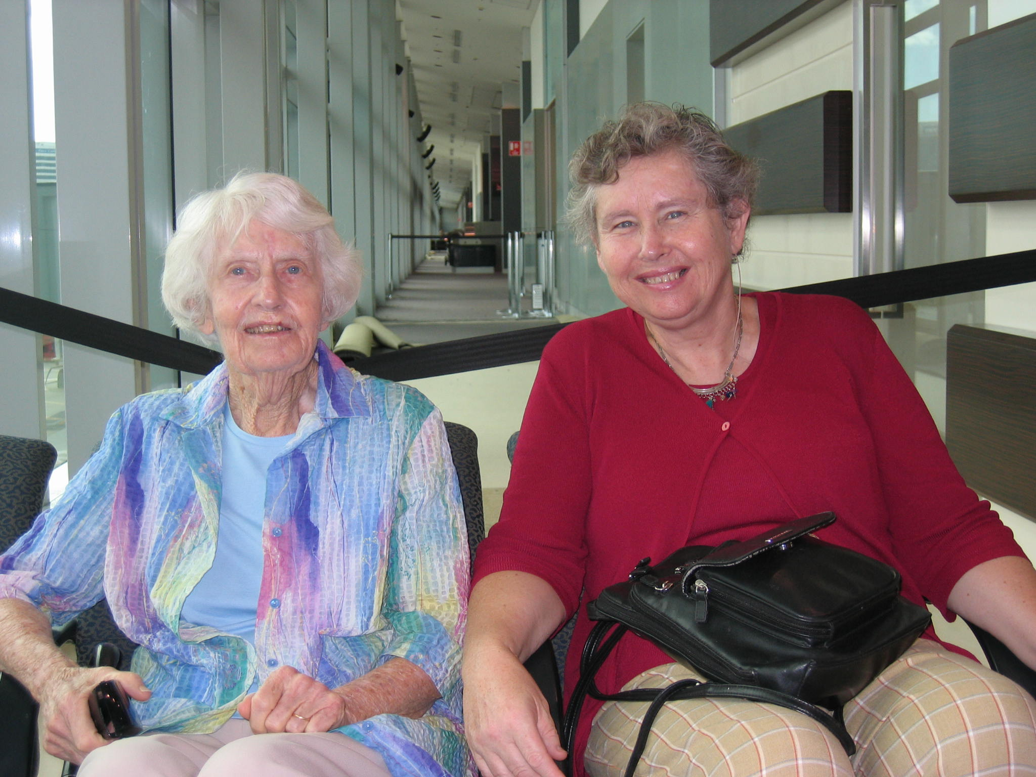 Photo of Helen (right) with her elderly mother (left) sitting down at an airport.