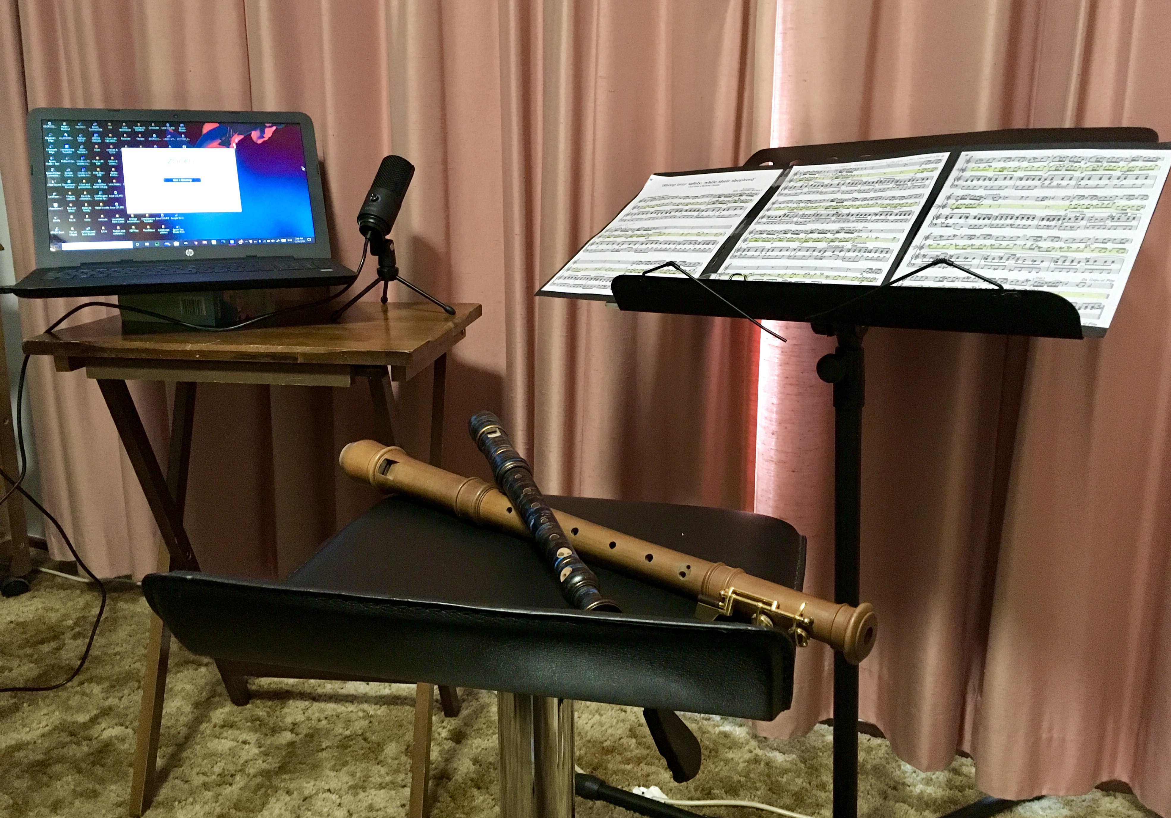 Photo of a room in Helen's house set up for music therapy over zoom. Photo includes a laptop sitting on a small table (left), music notes on a stand (right) Helen's Mollenhauer treble and   Moeck soprano recorders on a stool (middle).