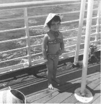 A greyscale photo of Helen as a young girl on a boat on her way to Australia. She is standing in front of the boat's railing and is wearing bathers and a hat.
