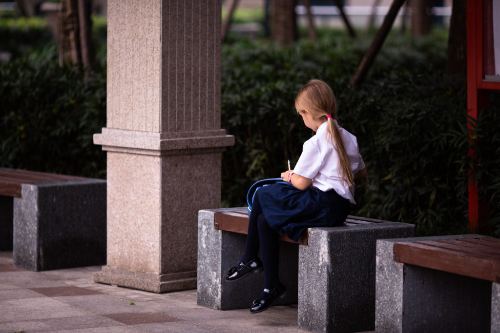 A young person wearing a school dress, sitting alone and not facing the camera.