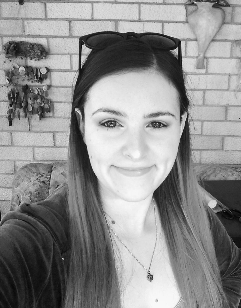 Greyscale photo of Bethany, a young woman with long brown hair and a necklace.