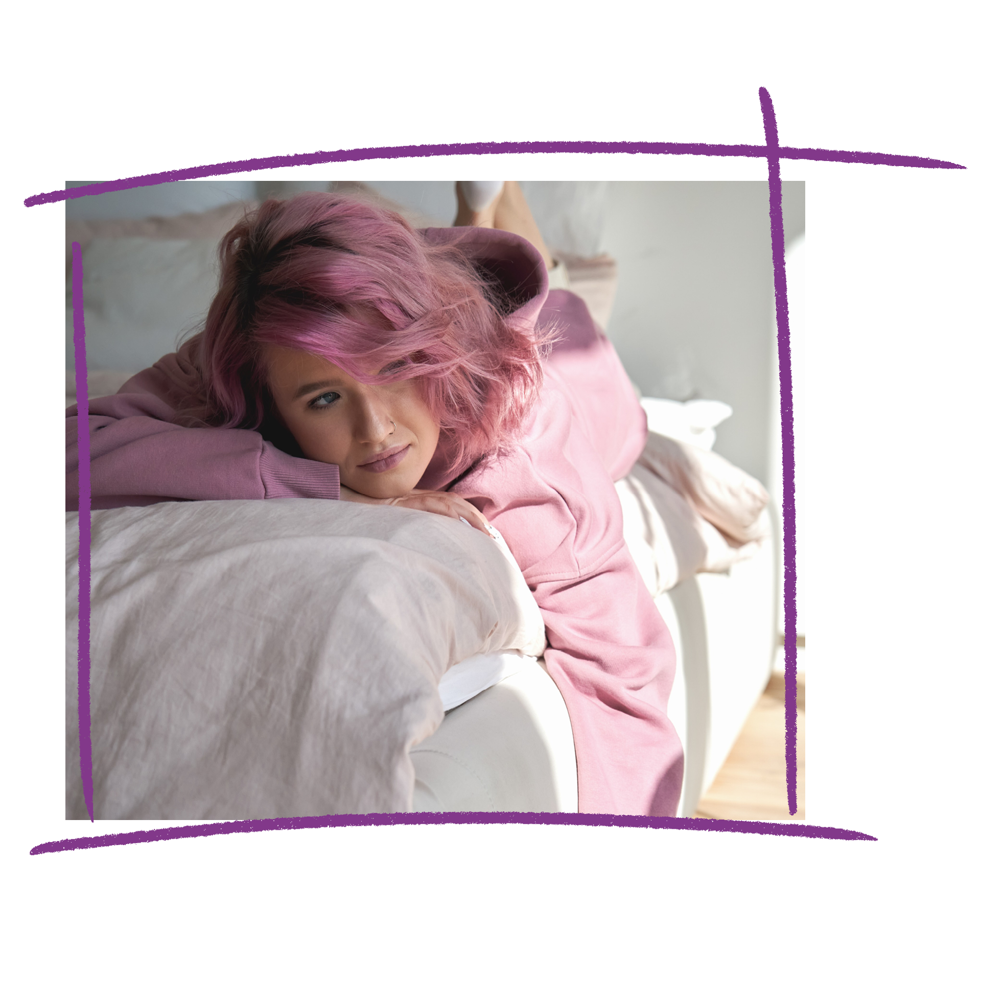 A woman with pink hair wearing a pink jumper lying on a couch.