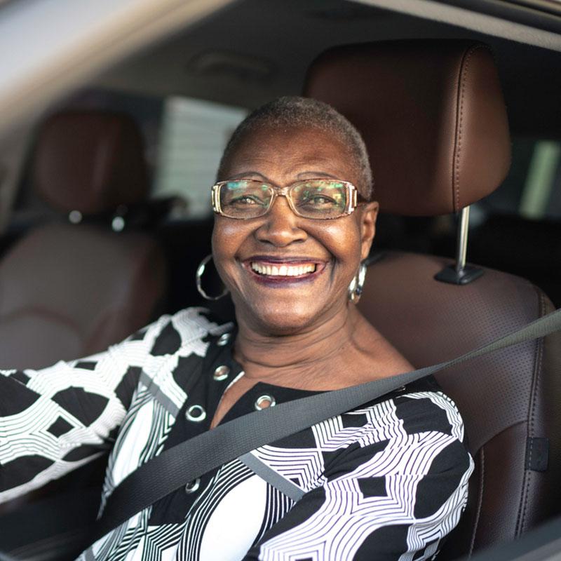 Happy senior citizen in her vehicle