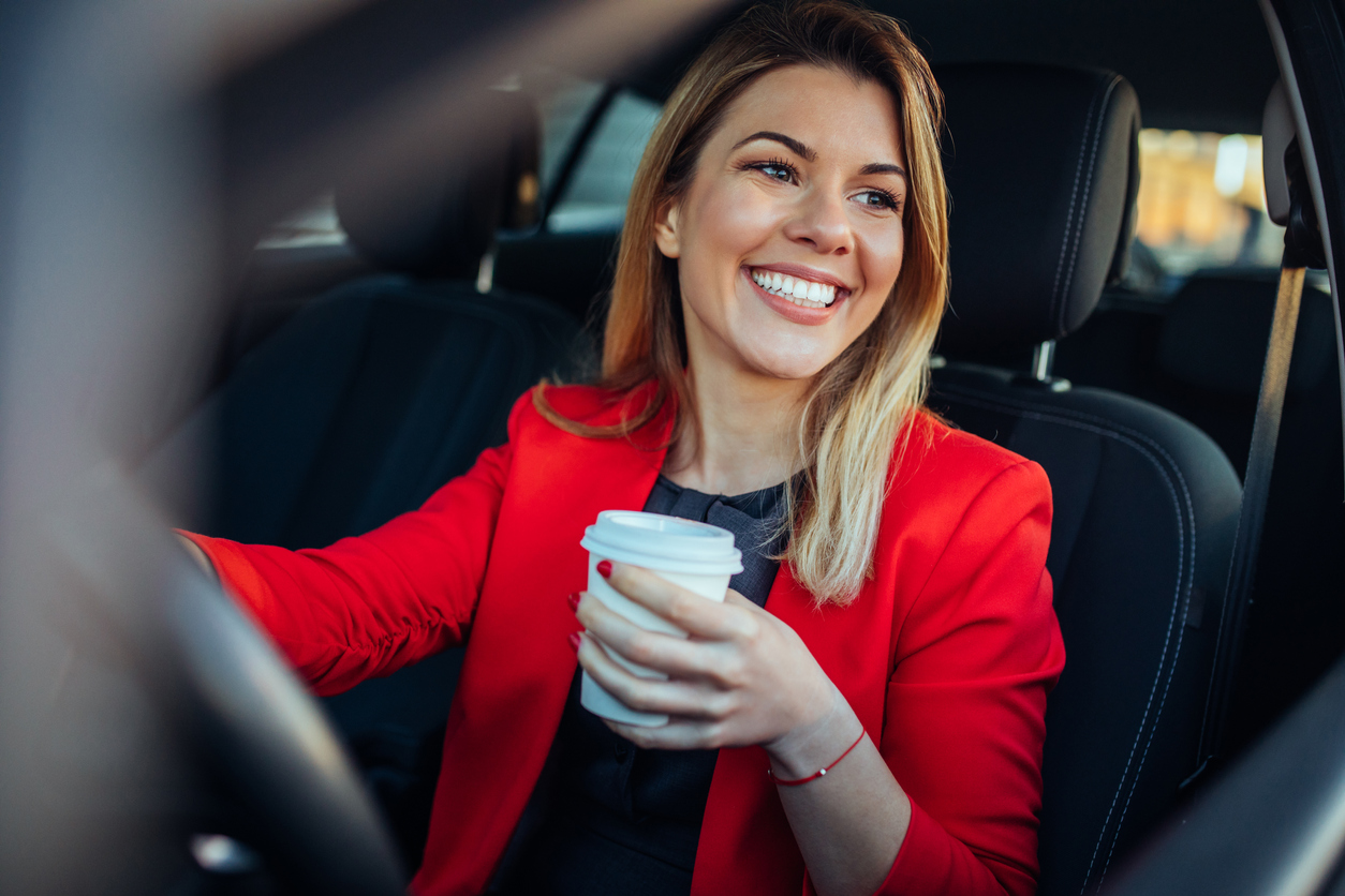 Happy woman drinking coffee in her car