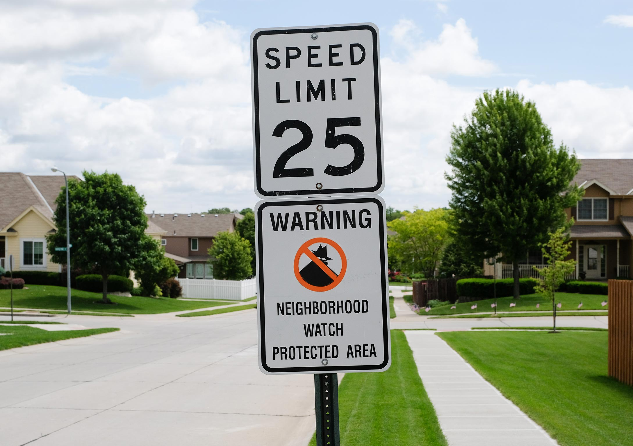 Speed limit and neighborhood watch sign on a pole