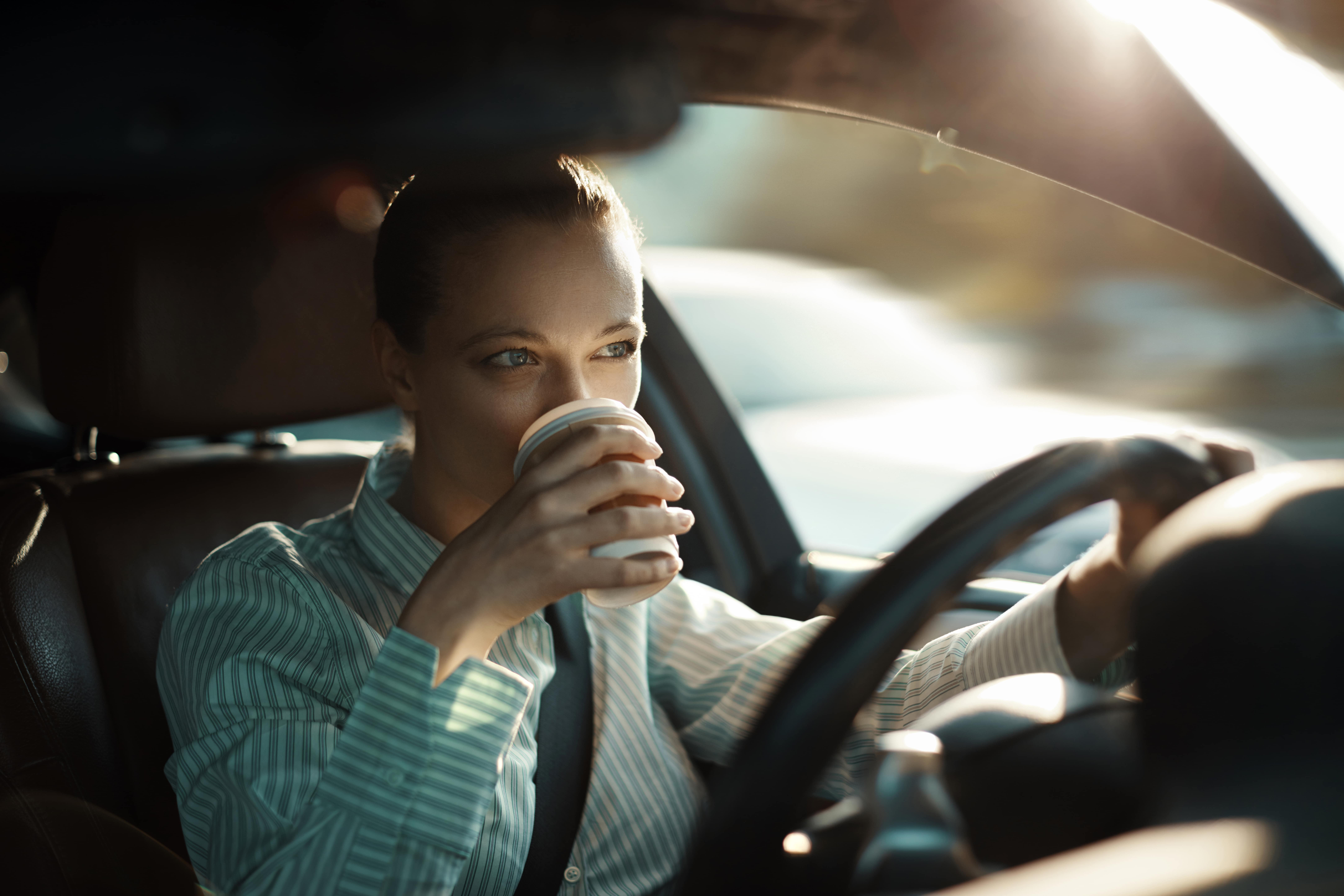 Woman sipping coffee in her vehicle