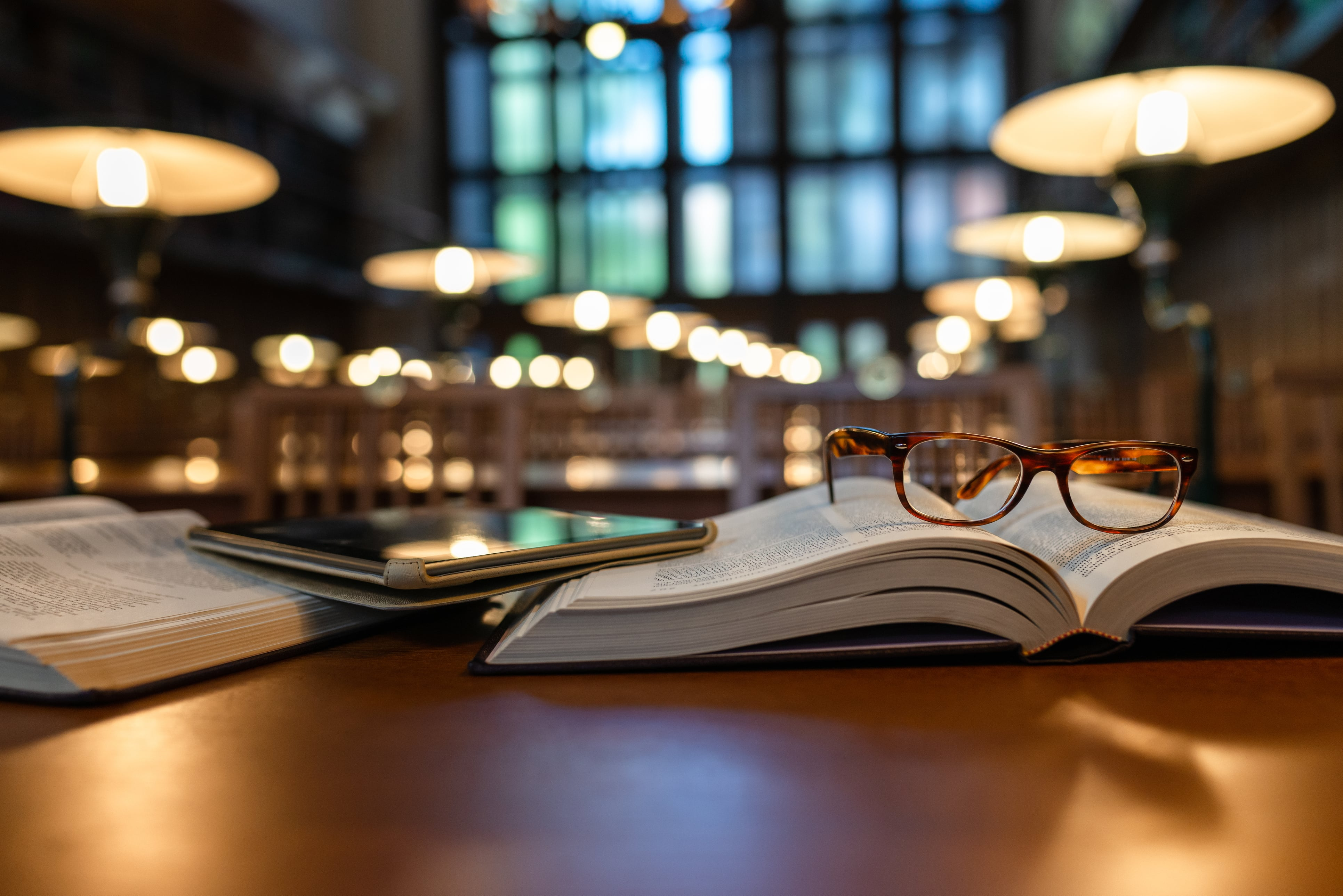 Pair of reading glasses left on an open book