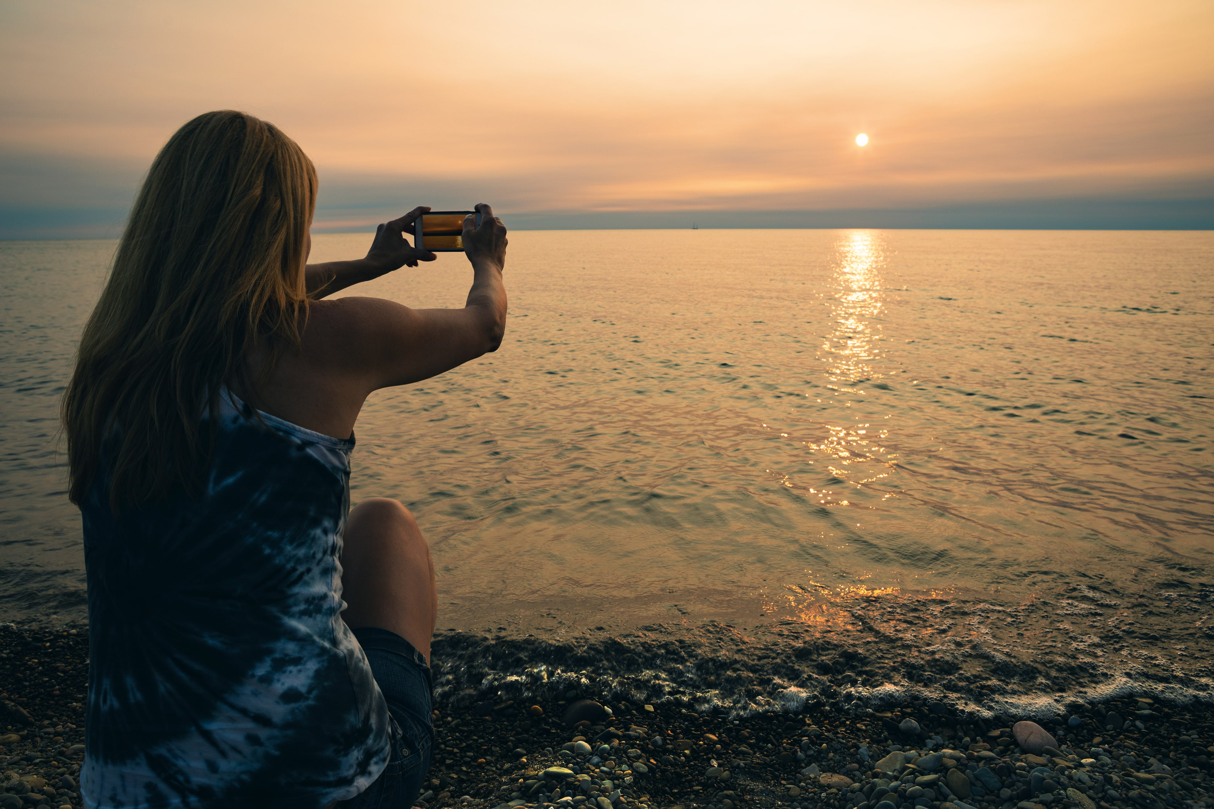 Woman on a beach taking a photo of the sunset
