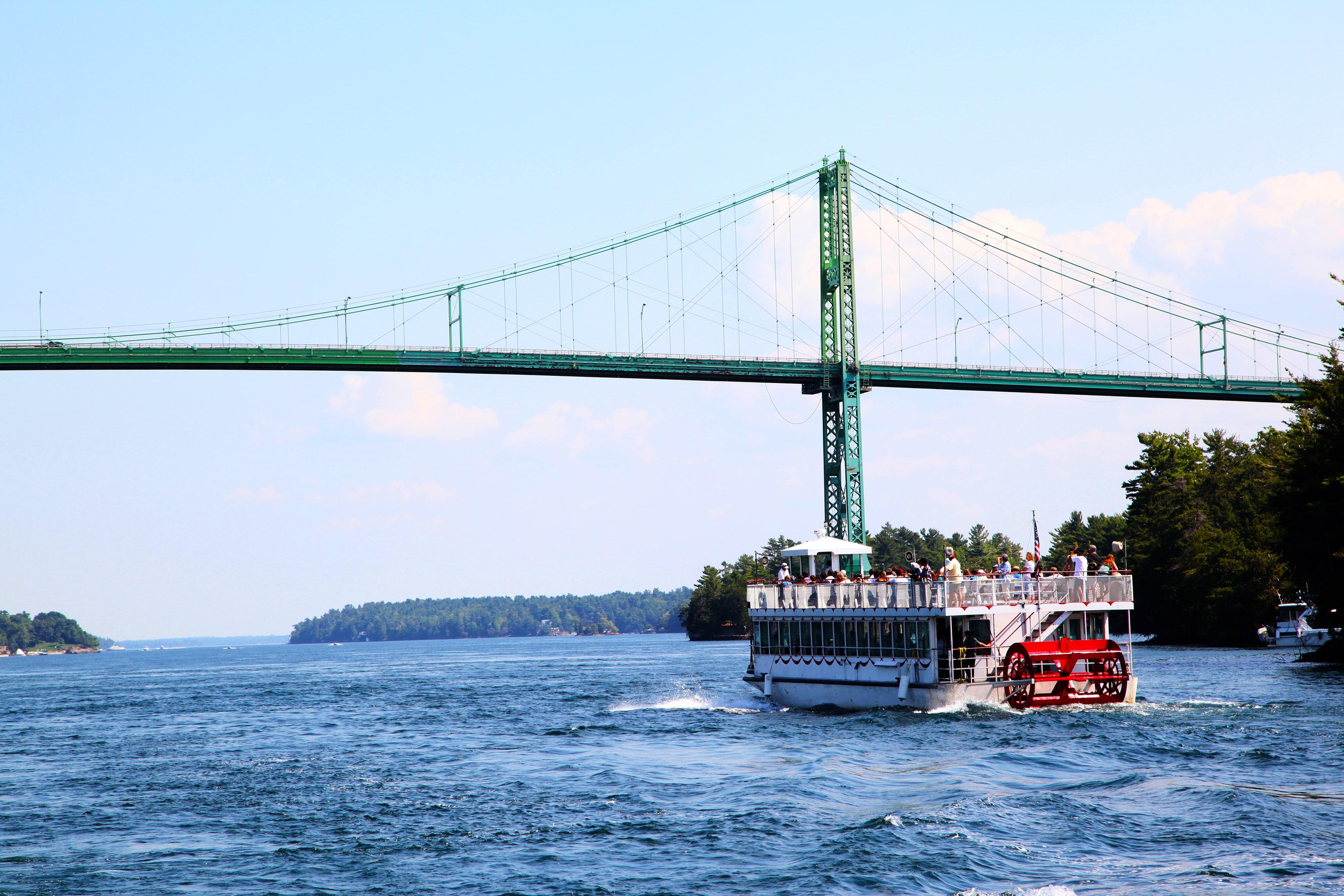 Tour boat passing under a scenic bridge