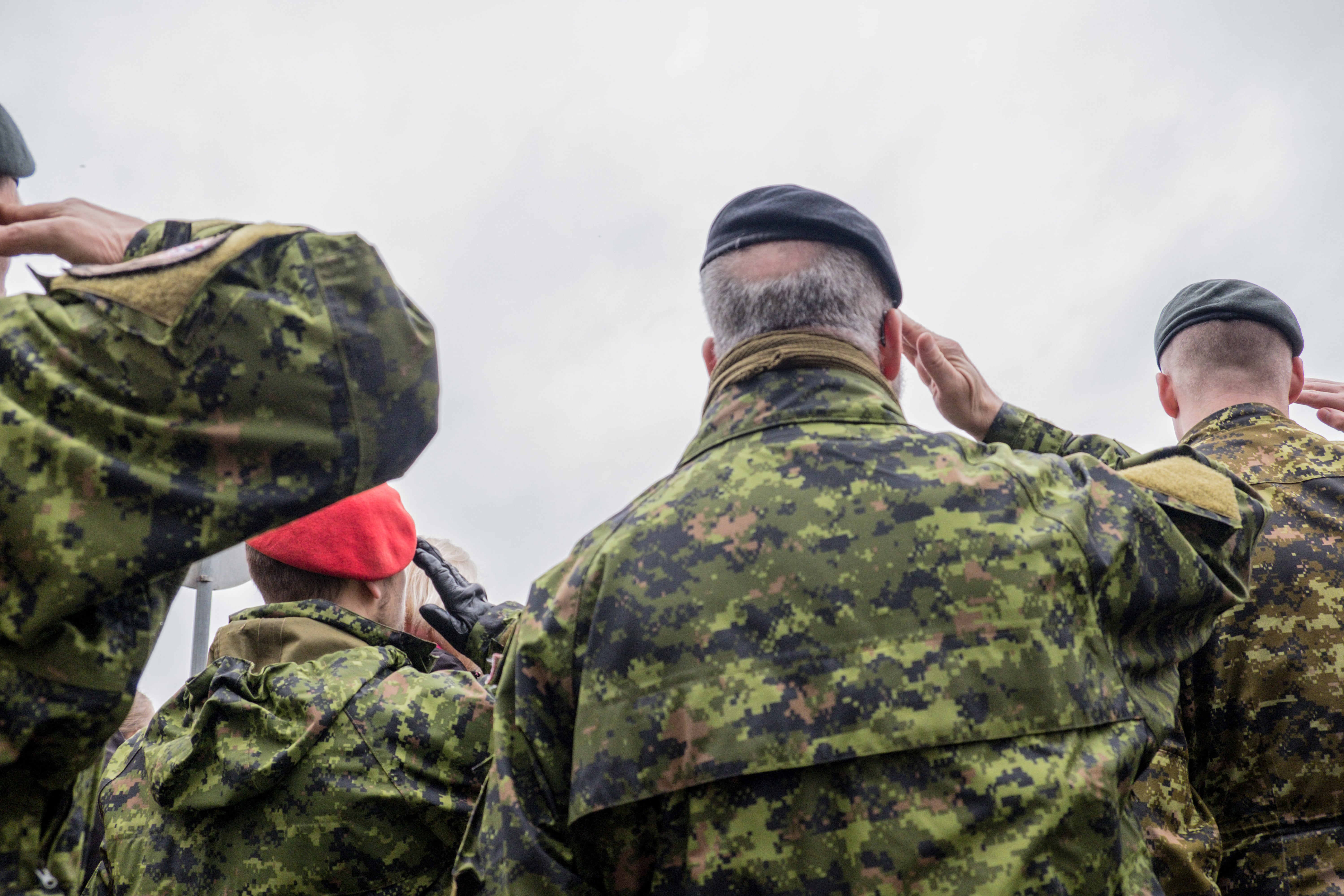 Canadian soldiers saluting in uniform