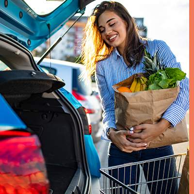 woman putting groceries in car