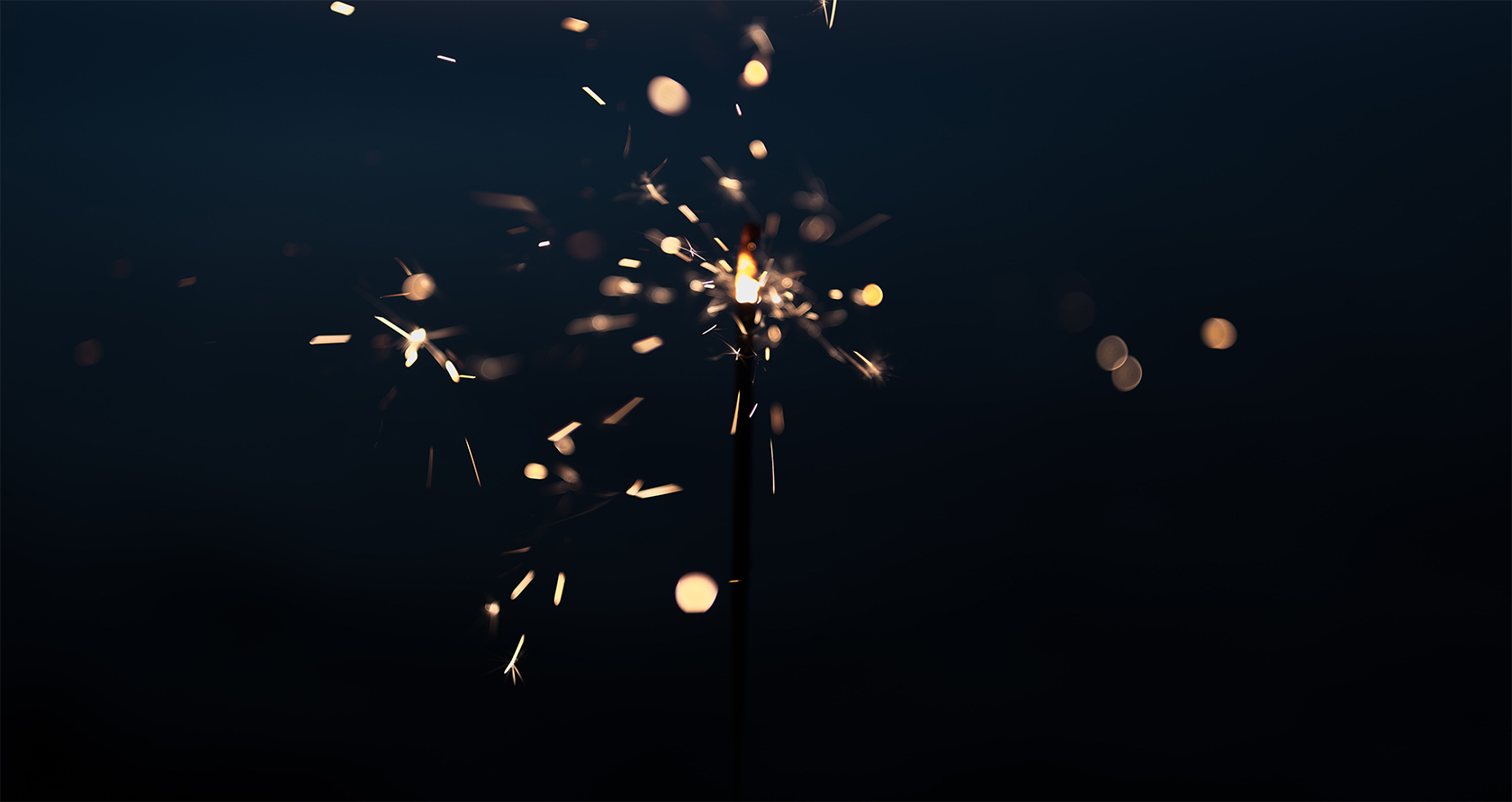 A Sparkler in the night time light up and shinning brightly