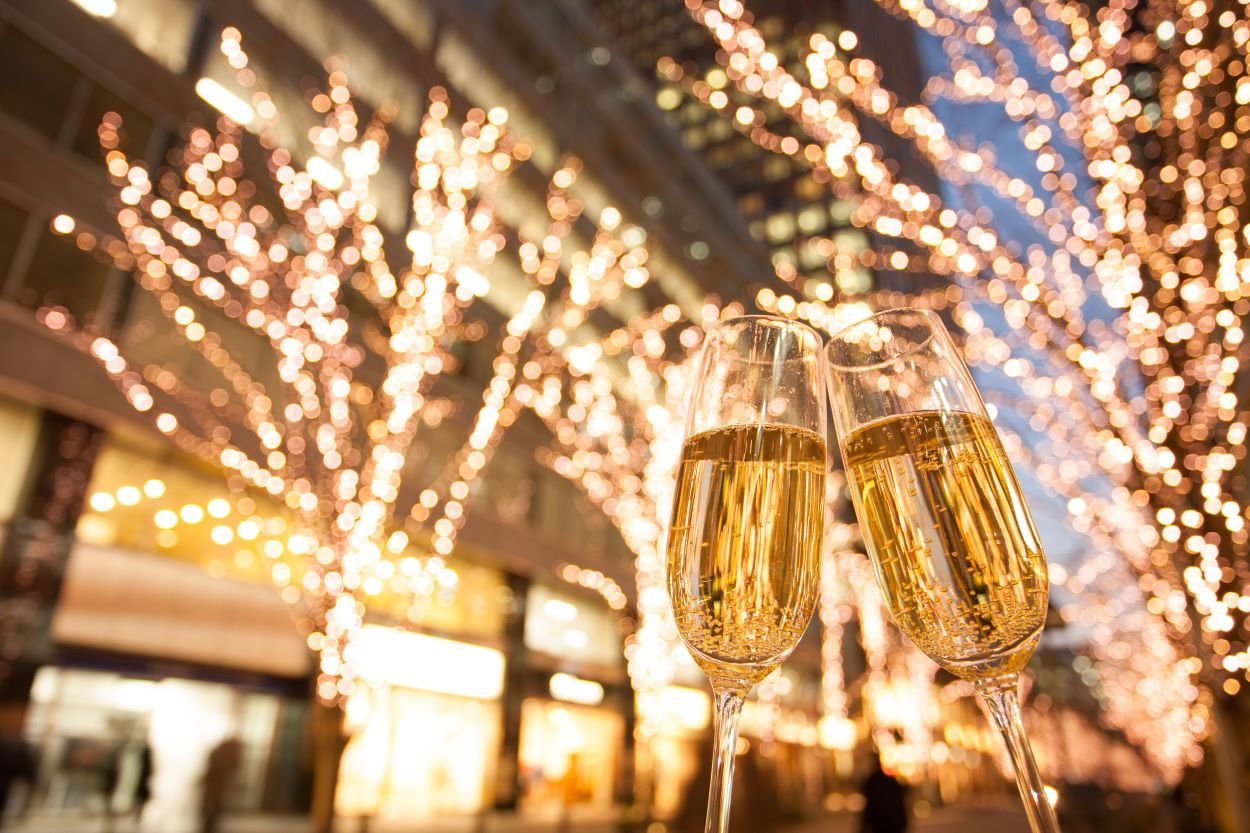Champagne glasses with Christmas illuminations | Where did the Tradition of Christmas Eve Dates Come From? | Christmas Eve Dates