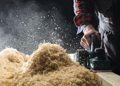 carpenter planing wood and creating hazardous dust
