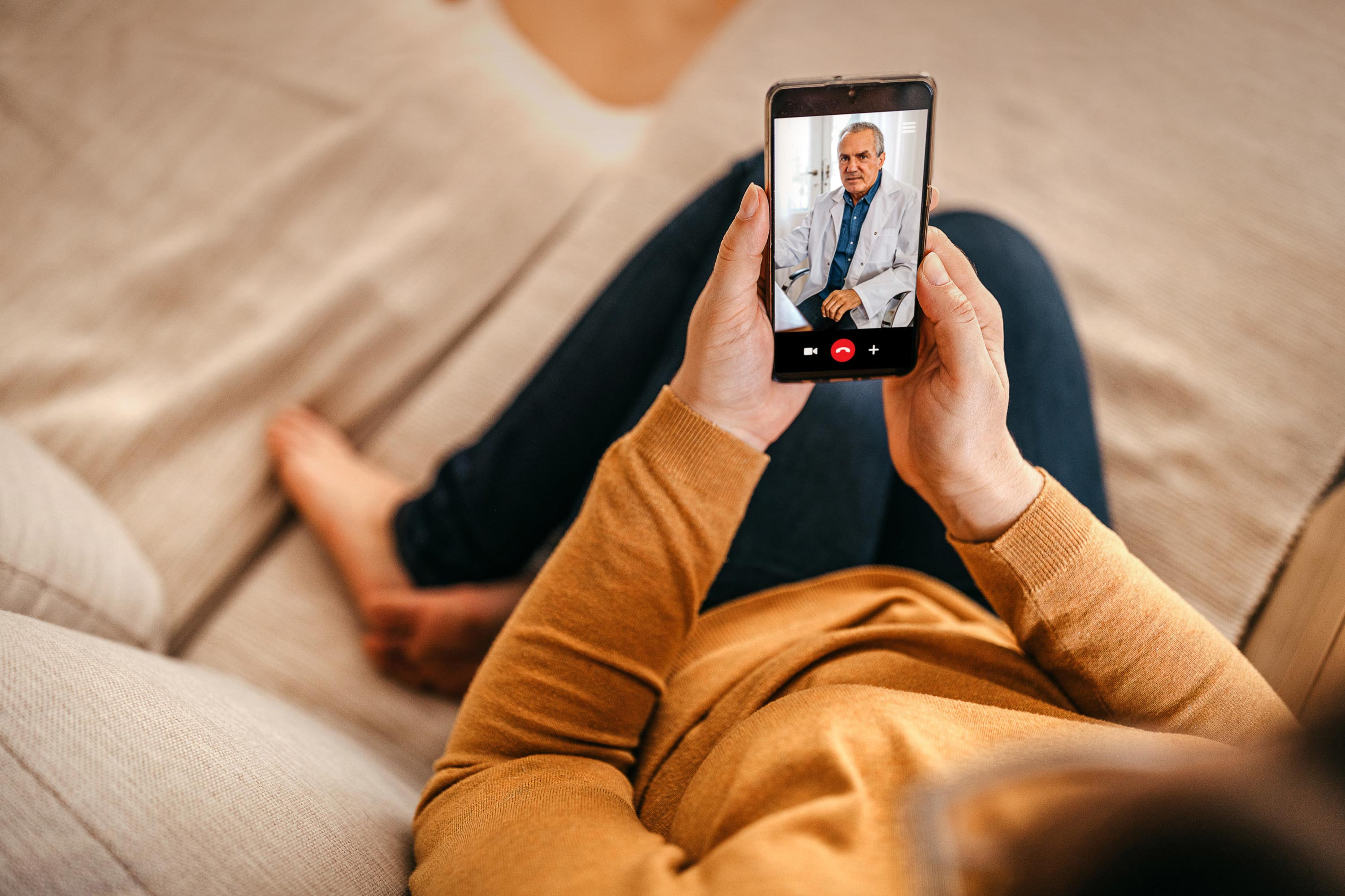 Picture of a woman at home using her cell phone for a telemedicine appointment