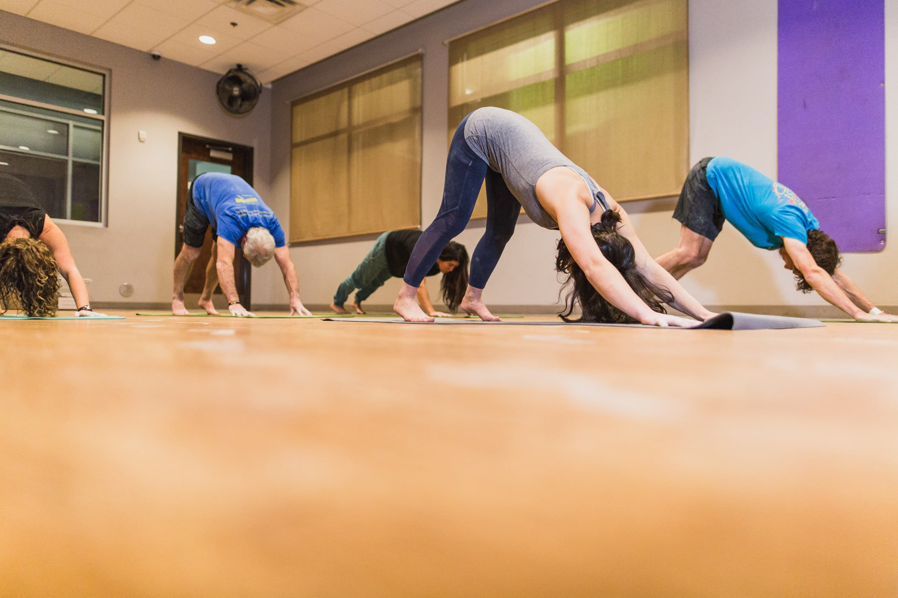 A group of women do yoga in an airy space.