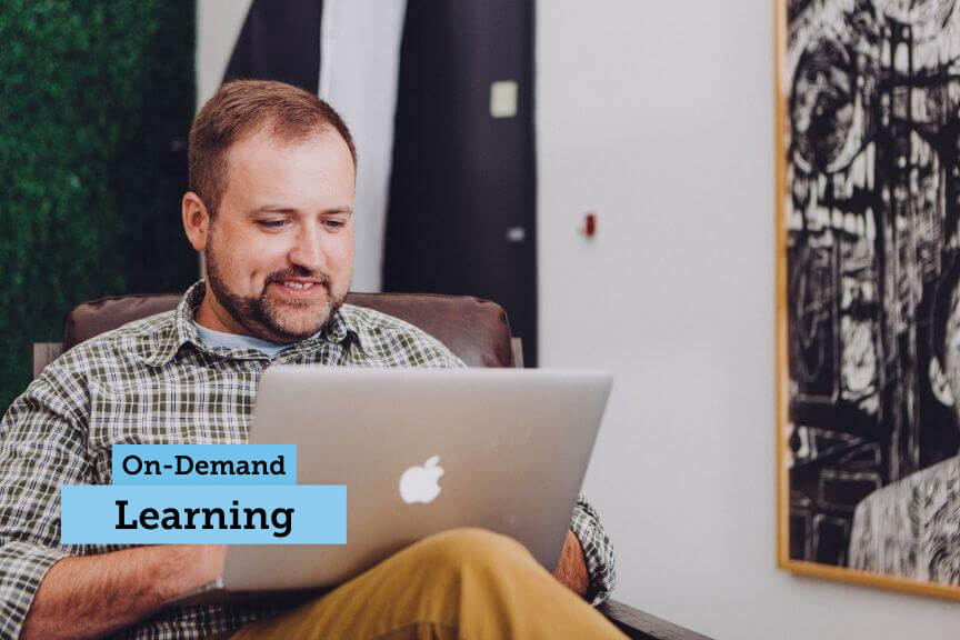 """Man in chair with a laptop with words """"On-Demand Learning"""""""