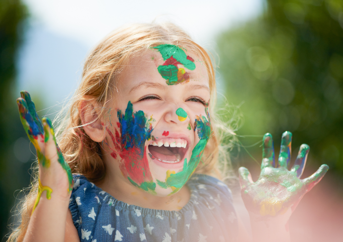 Little girl with paint on her face and hands laughing.