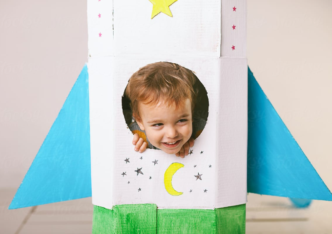 Small boy peeking out of hand-crafted rocket ship.