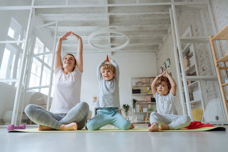 Mom and her two sons practicing yoga together.