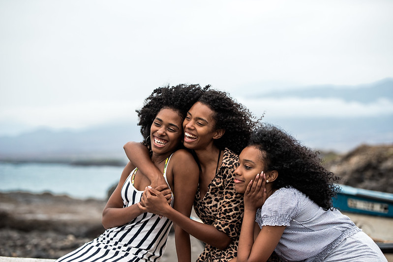 Mom and her two teenage daughters at the seaside.