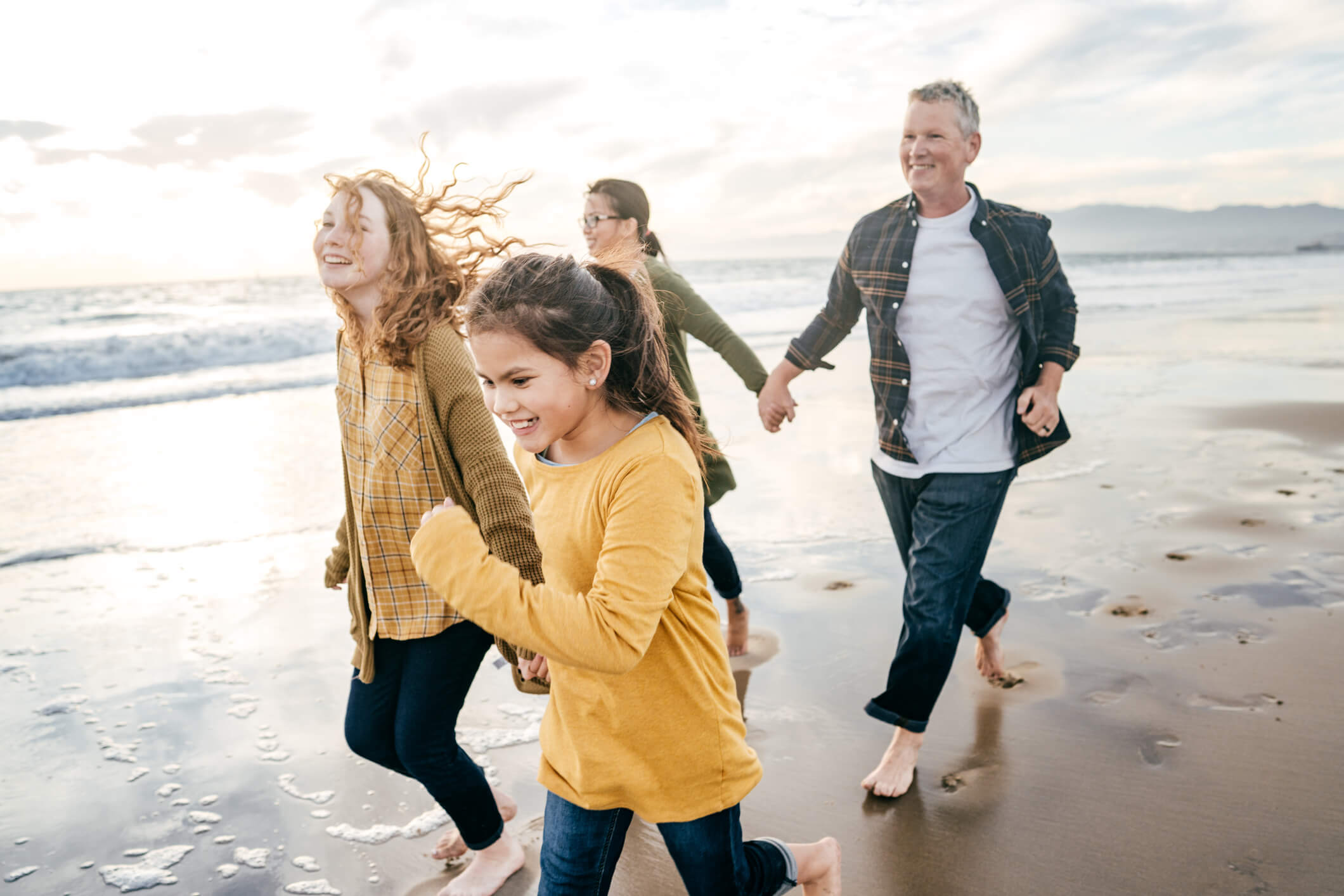 Family of four walking on the beach together