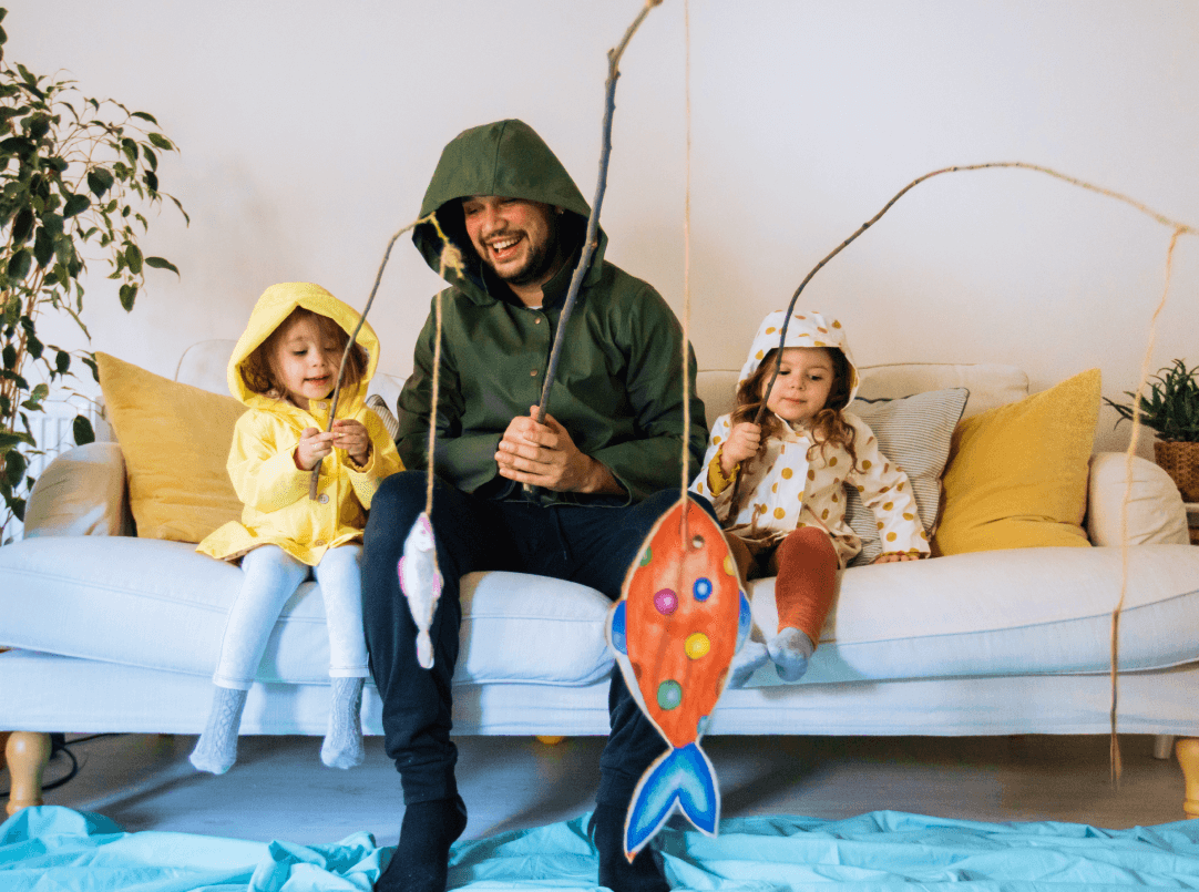 Father and his two daughters pretending to fish by playing with fish made out of cardboard.
