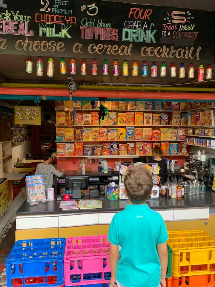 boy at the cereal killer cafe in london standing in front of milk and cereal