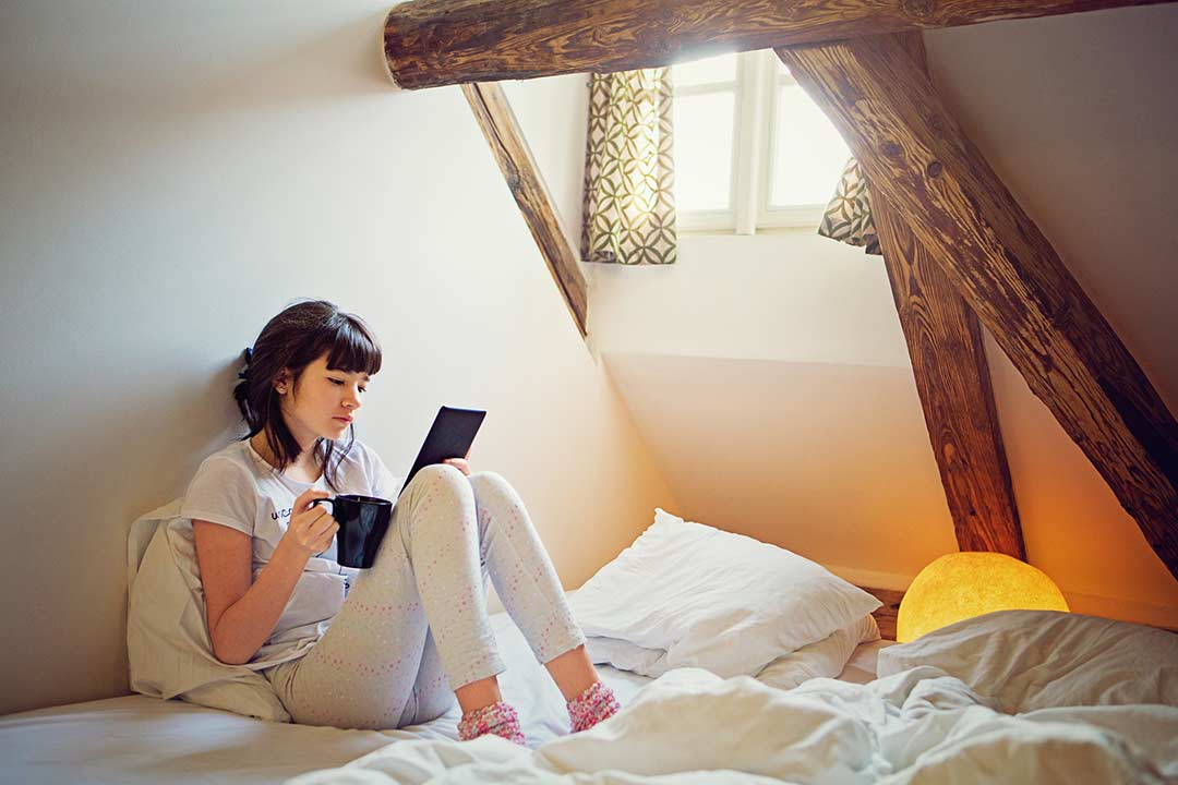 A teenage girl relaxing on her bed reading a story.