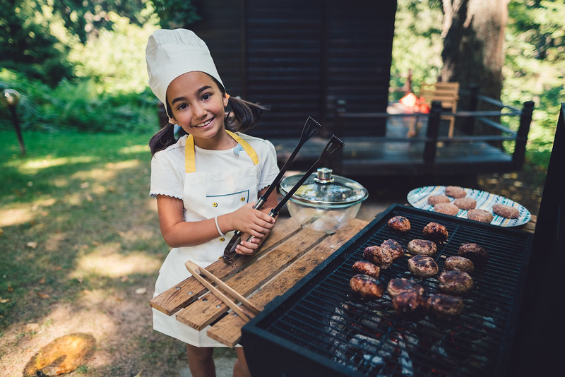 A young girl learning how to barbecue.