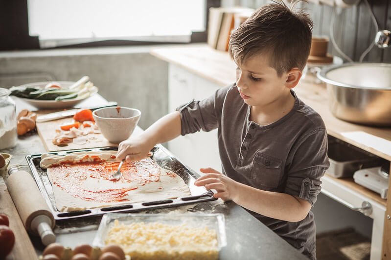Young boy making pitta pizza