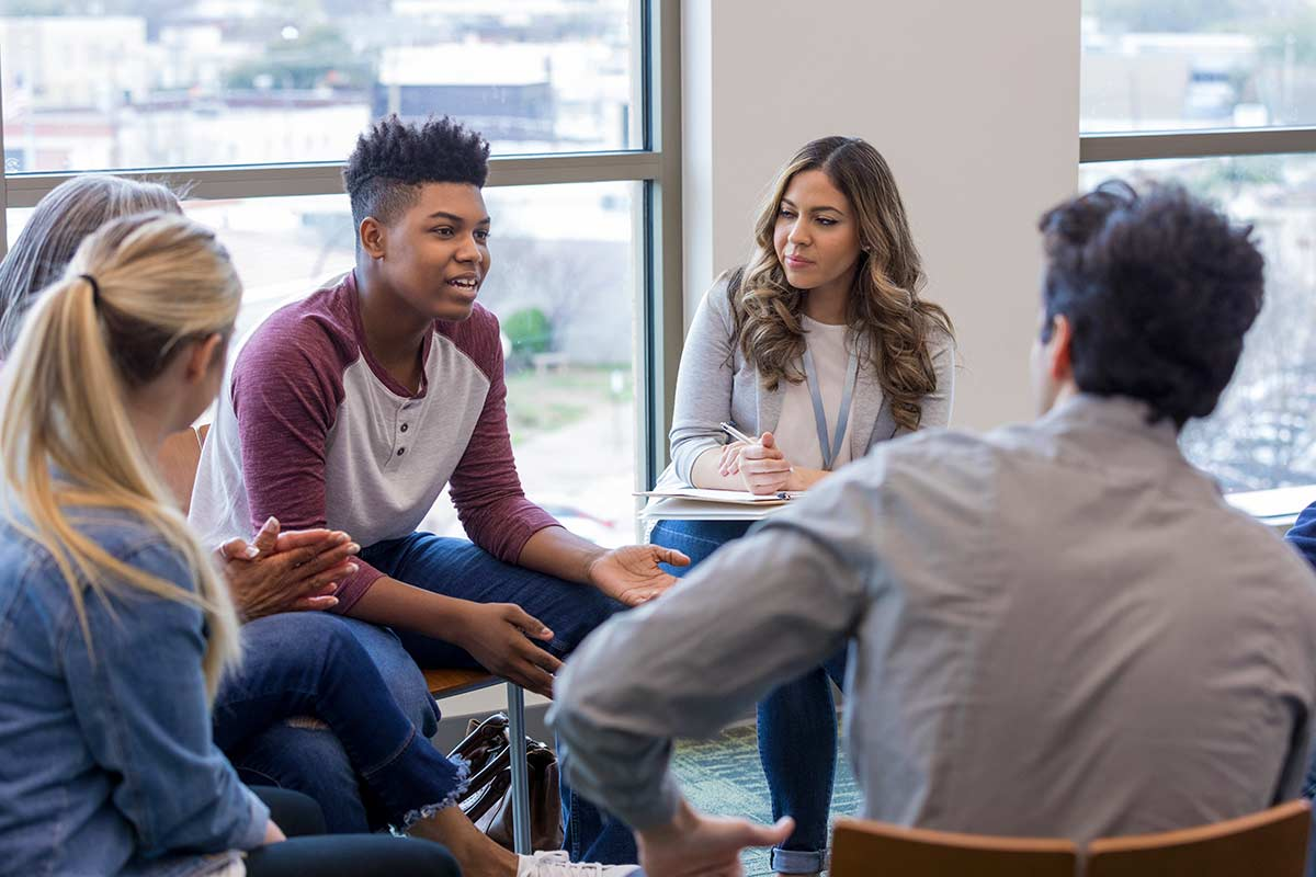 Teens sat in a circle debating a contentious topic.