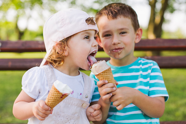 Baby boy shares an ice cream with his sister during the bank holiday weekend