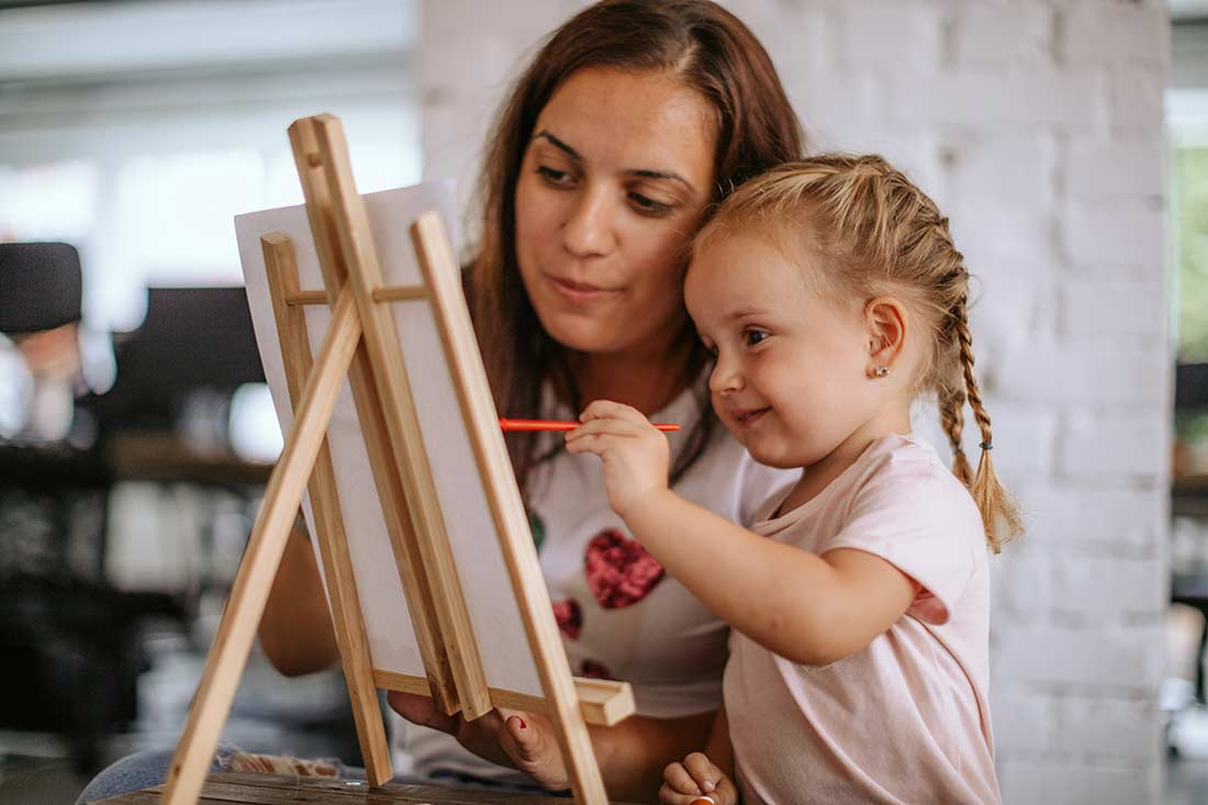 A young girl taking part in an art event and showing off her painting skills.
