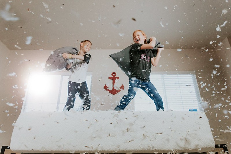 Two boys play-fighting with pillows.