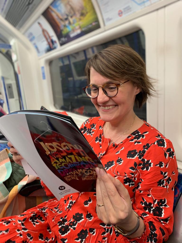 A woman reading the show programme from Joseph the Musical on the tube