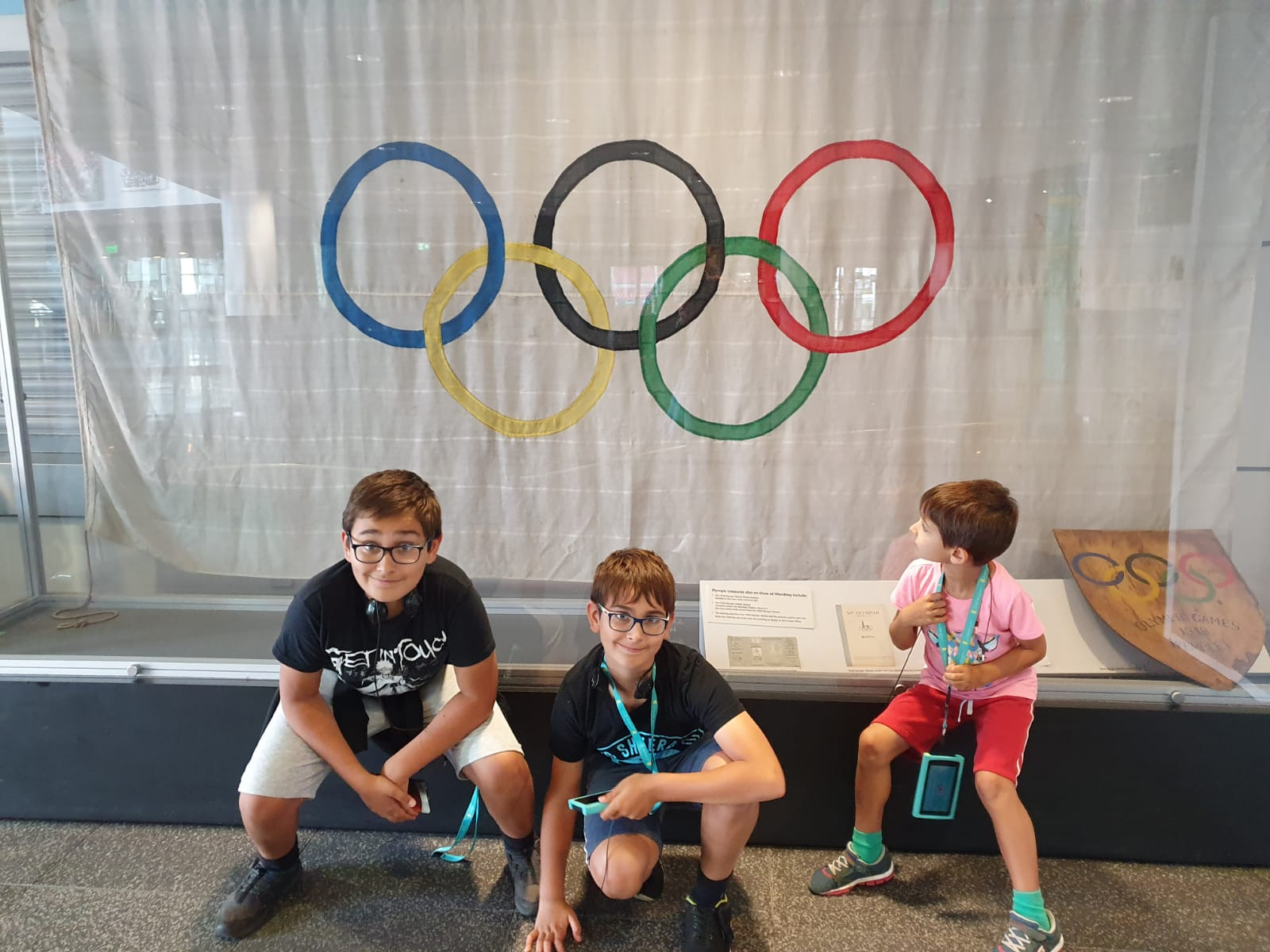 Three kids sat near the Olympics flag at Wembley Stadium
