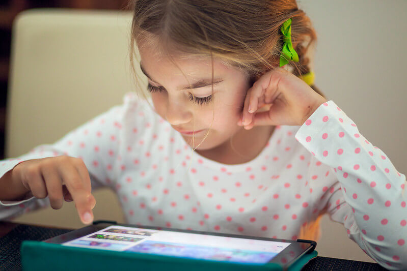 A young girl using a tablet to learn at home.