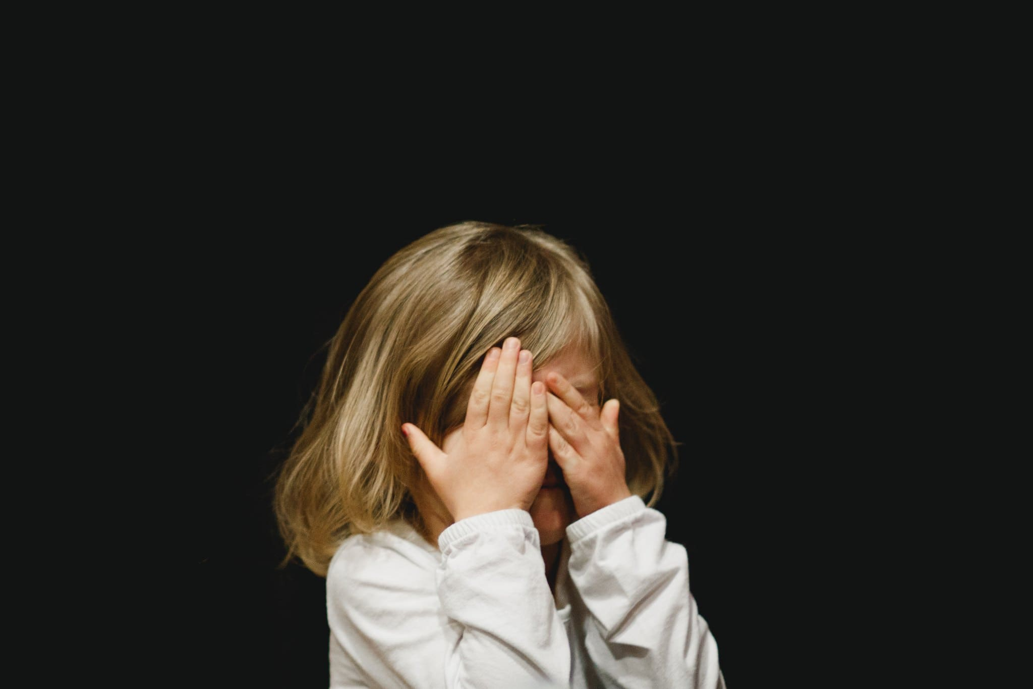 A child hiding behind her hands, nervous to speak in front of a group.