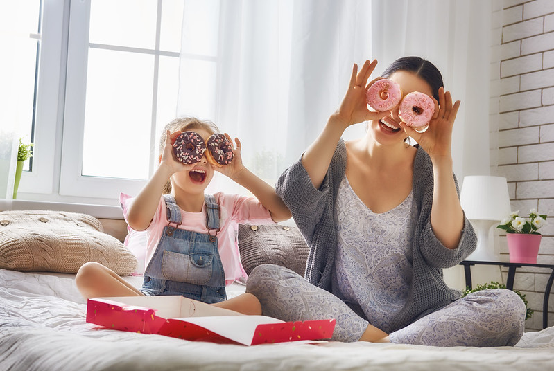 A mother and daughter playing with homemade doughnuts.