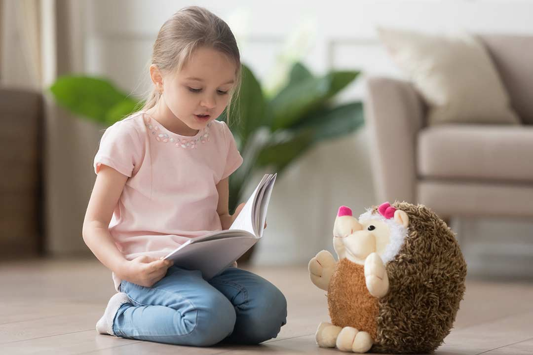 A girl reading a story to her teddy for her at-home book club.