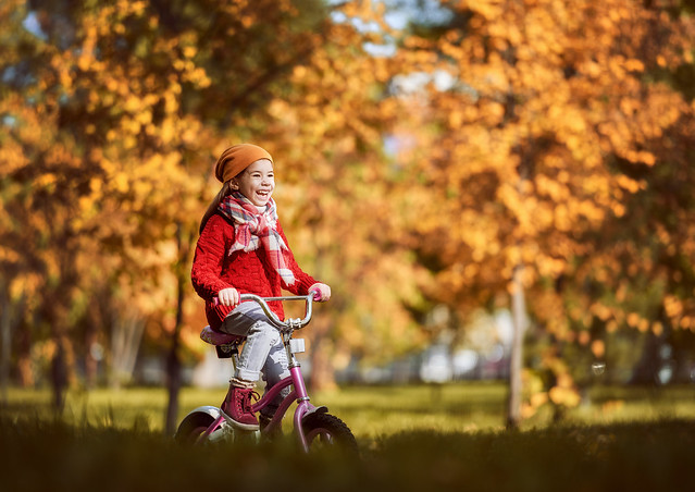 Young girl riding her bike in the park in Autumn