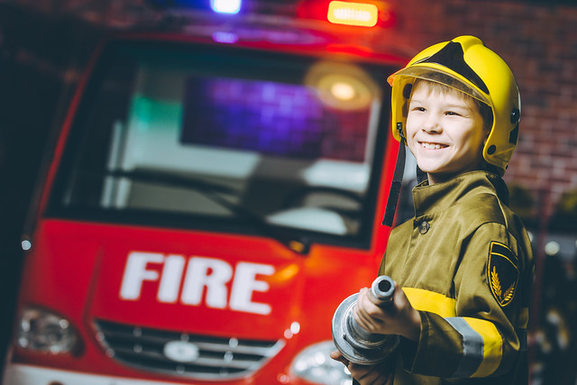 boy dressed up as a firefighter in front of fire engine