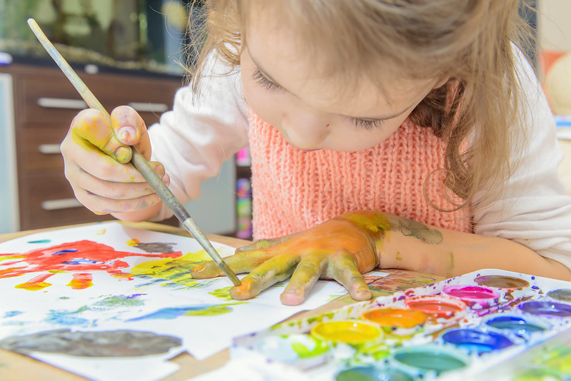 Young girl enjoying messy play and painting on her hand.