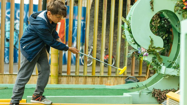 boy hitting a golf ball on plonk crazy golf course