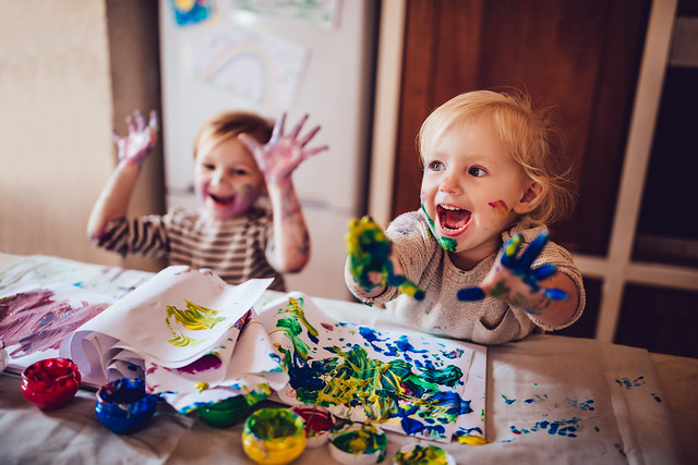 Two young children enjoying finger painting.