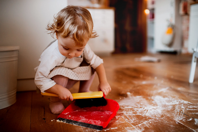 Toddler using a dustpan and brush on the kitchen floor.